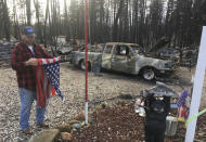 FILE - In this Dec. 5, 2018, file photo, Jerry McLean folds the flag that was flying outside the remains of his home in Paradise, Calif. The home McLean shared with his wife, Joyce, is one of nearly 9,000 Paradise homes destroyed in the deadliest and most destructive wildfire in California history. (AP Photo/Don Thompson, File)