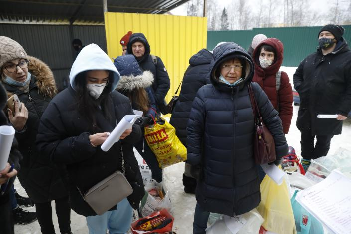 Relatives and friends of jailed protesters wait to transfer food and warm clothes at the deportation centre Sakharovo, 70km (43,7 miles) south-west of Moscow which was urgently transformed into a detention center in the absence of prison space where she has spent 3 days outside Moscow, Russia, Wednesday, Feb. 3, 2021. (AP Photo/Pavel Golovkin)