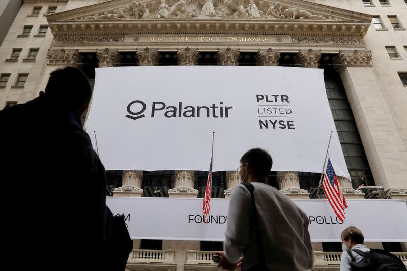 FILE PHOTO: People walk by a banner featuring the logo of Palantir Technologies (PLTR) at the New York Stock Exchange (NYSE) on the day of their initial public offering (IPO) in Manhattan, New York City