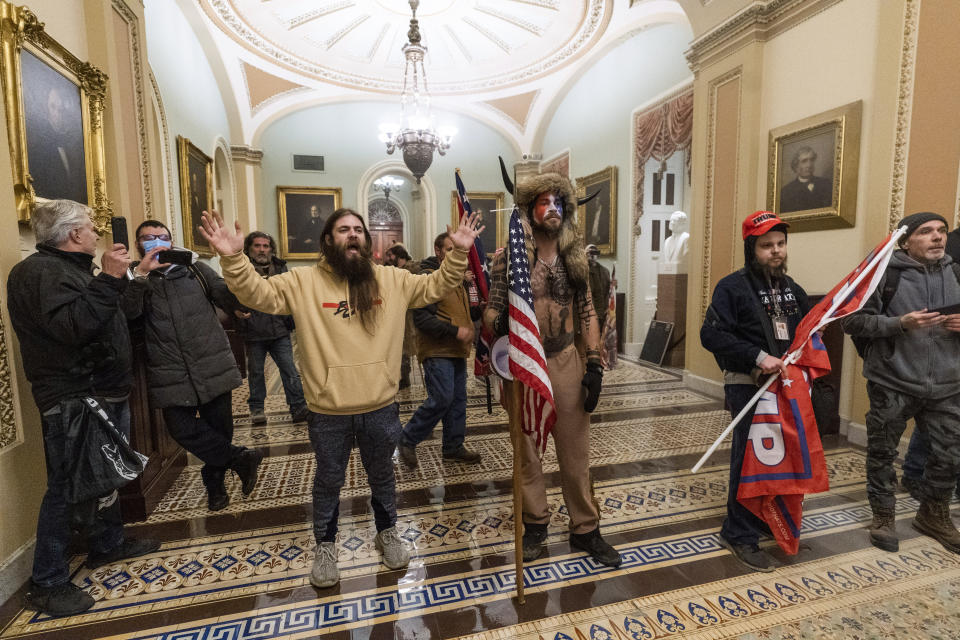 FILE - In this Wednesday, Jan. 6, 2021 file photo supporters of President Donald Trump are confronted by U.S. Capitol Police officers outside the Senate Chamber inside the Capitol in Washington. Jacob Anthony Chansley, the Arizona man with the painted face and wearing a horned, fur hat, was taken into custody Saturday, Jan. 9, 2021 and charged with counts that include violent entry and disorderly conduct on Capitol grounds. (AP Photo/Manuel Balce Ceneta, file)