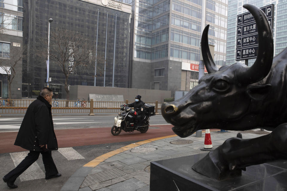In this photo taken Thursday, Feb. 13, 2020, a man walks past a bull sculpture on a quiet street Beijing, China. Millions of Chinese workers and entrepreneurs are bearing the rising costs of an anti-virus campaign that has shut down large sections of the economy. The government has imposed restrictions nationwide that have stalled travel and sales of real estate and autos. (AP Photo/Ng Han Guan)