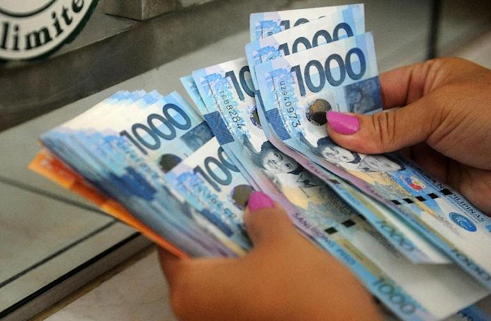 The Filipino peso hit a seven-year low to the dollar on Monday and foreign investors pulled out from local shares for a 23rd straight day (AFP Photo/Jay Directo)