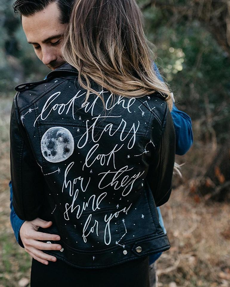 We're obsessed this edgy leather jacket that's emblazoned with a celestial setting and romantic lyrics.