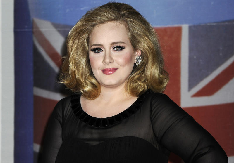 "FILE - In this Feb. 21, 2012 file photo, performer Adele arrives for the Brit Awards 2012 at the O2 Arena in London.  The 24-year-old British songstress' album ""21"" has sold more than 10 million copies, according to Nielsen SoundScan. The album reached the milestone the week of Nov. 19, 2012, less than two years after its release.  (AP Photo/Jonathan Short, File)"