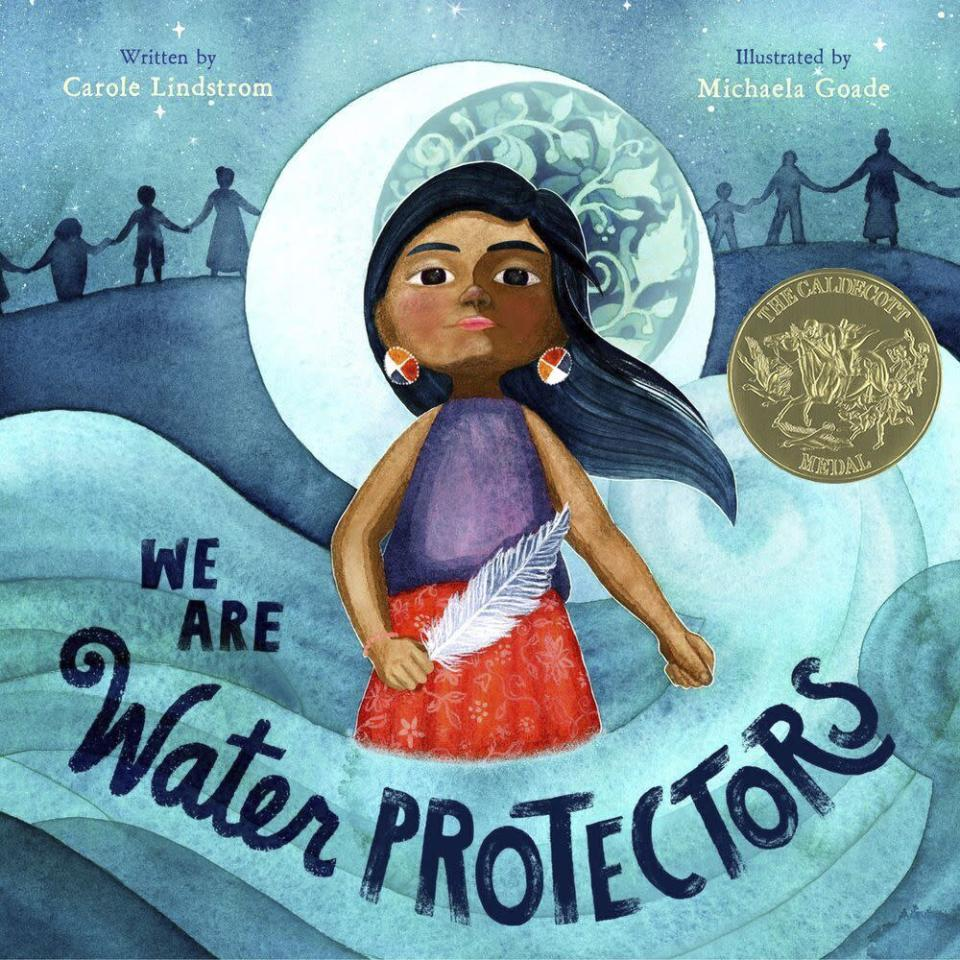 "This cover image released by Roaring Brook Press shows ""We Are Water Protectors,"" written by Carol Lindstrom and illustrated by Michaela Goade. Goade became the first Native American to win the prestigious Randolph Caldecott Medal for best children's picture story. Goade is a member of the Tlingit and Haida Indian tribes in Southeast Alaska. ""We Are Water Protectors,"" is a call for environmental protection that was conceived in response to the planned construction of the Dakota Access Pipeline through Standing Rock Sioux territory. (Roaring Brook Press via AP)"