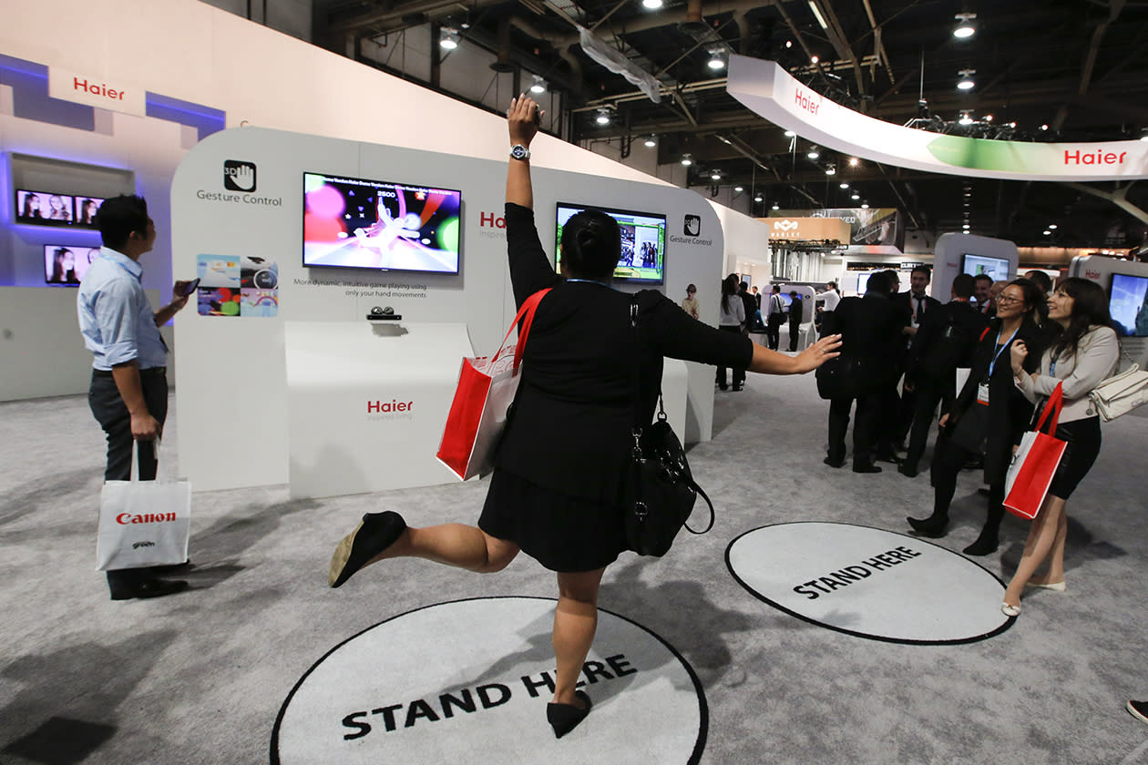 A show attendee tries out Haier's gesture control TV at the Haier booth at the International Consumer Electronics Show.