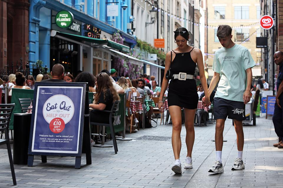 A general view of an Eat Out to Help Out sign outside of a busy restaurant on Kingly Street, London.