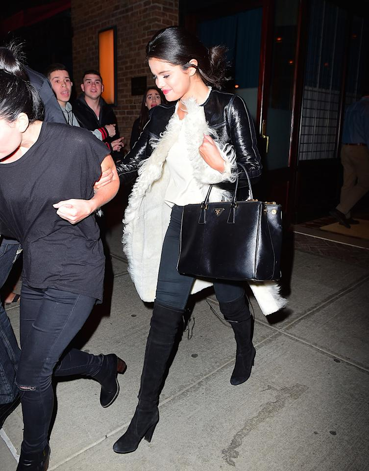 <p>Selena Gomez dressed up a casual white T-shirt with the boots and a furry leather coat during a night out in New York. <em>(Photo: Splash News)</em> </p>