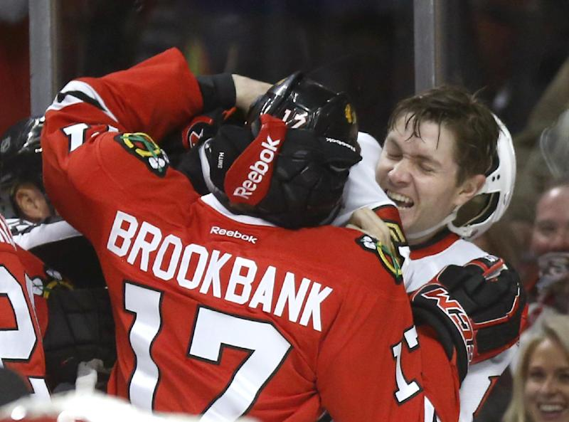 Chicago Blackhawks defenseman Sheldon Brookbank (17) scuffles with Ottawa Senators center Zack Smith during the first period of an NHL hockey game Tuesday, Oct. 29, 2013, in Chicago. (AP Photo/Charles Rex Arbogast)