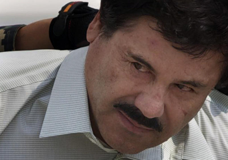 """Joaquin """"El Chapo"""" Guzman is escorted to a helicopter in handcuffs by Mexican navy marines at a navy hanger in Mexico City, Saturday, Feb. 22, 2014. A senior U.S. law enforcement official said Saturday, that Guzman, the head of Mexico's Sinaloa Cartel, was captured alive overnight in the beach resort town of Mazatlan. Guzman faces multiple federal drug trafficking indictments in the U.S. and is on the Drug Enforcement Administrationís most-wanted list. (AP Photo/Eduardo Verdugo)"""
