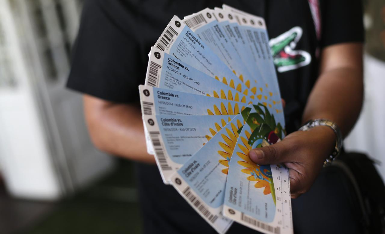 A Colombian fan displays his FIFA 2014 World Cup tickets for the match between Colombia and Greece, in Rio de Janeiro April 18, 2014. FIFA Venue Ticketing Centres opened in host cities on Friday. REUTERS/Ricardo Moraes (BRAZIL - Tags: SPORT SOCCER WORLD CUP)