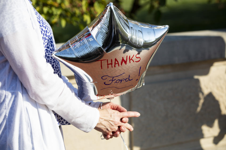 """A woman holds a sliver balloon with a hand written message """"Thanks Ford!"""" during a news conference in front of the capital in Frankfort, Ky., Tuesday, Sept. 28, 2021, announcing that Ford is building a battery manufacturing plant in Hardin County. (Silas Walker/Lexington Herald-Leader via AP)"""
