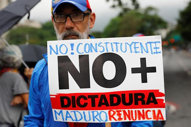 """<p>An opposition supporter holds a placard that reads """"No to the constituent assembly. No more dictatorship. Maduro, resign"""" during a protest against Venezuela's President Nicolas Maduro's government in Caracas, Venezuela May 2, 2017. (Photo: Carlos Garcia Rawlins/Reuters) </p>"""