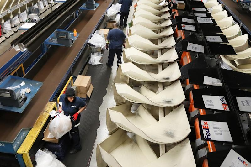 Employees sort packages inside FedEx's superhub at the Memphis International Airport on Tuesday, November 20, 2018.