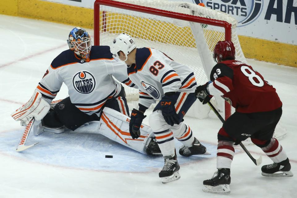 Edmonton Oilers goaltender Mikko Koskinen, left, gets help from Oilers defenseman Matt Benning (83) on a shot by Arizona Coyotes right wing Conor Garland (83) during the first period of an NHL hockey game Tuesday, Feb. 4, 2020, in Glendale, Ariz. (AP Photo/Ross D. Franklin)