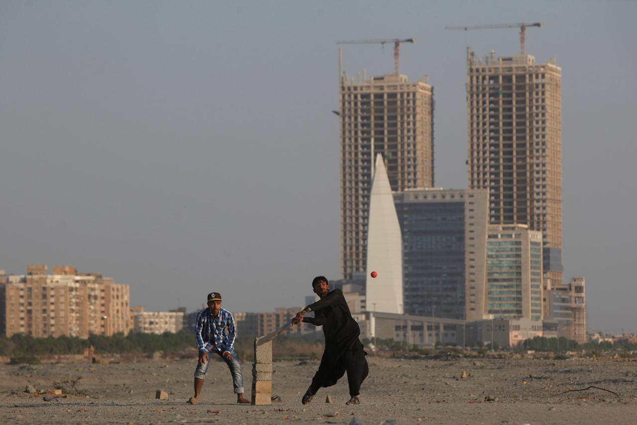People play cricket with the Hyperstar shopping mall and under construction buildings in the background, in Karachi, Pakistan November 20, 2017. REUTERS/Akhtar Soomro