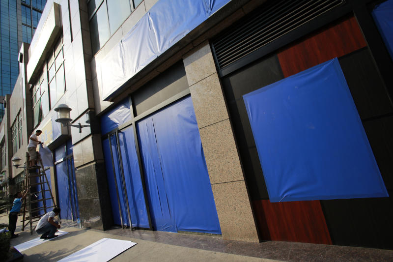 Workers cover signboards of several Japanese restaurants with blue sheets ahead of major protests expected on Tuesday, near the Japanese Consulate General Monday Sept. 17, 2012 in Shanghai, China. China moved to tamp down rising anti-Japan sentiment after a weekend of sometimes violent demonstrations, threatening Monday to arrest lawbreakers and scrubbing websites of protest-related images and posts. (AP Photo/Eugene Hoshiko)