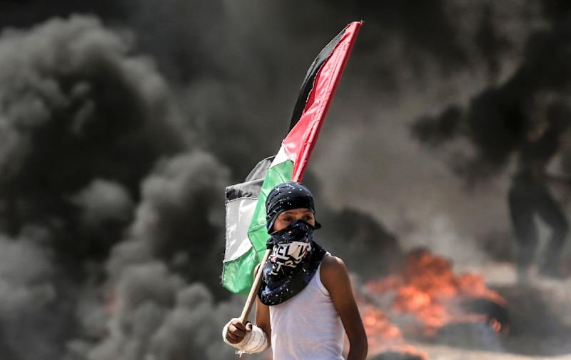 A Palestinian boy holds a flag during protests near the border between the Gaza Strip and Israel on May 14, 2018 (AFP Photo/MAHMUD HAMS)
