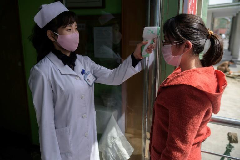 A health worker takes the temperature of a woman at an entrance of the Pyongchon District People's Hospital in Pyongyang