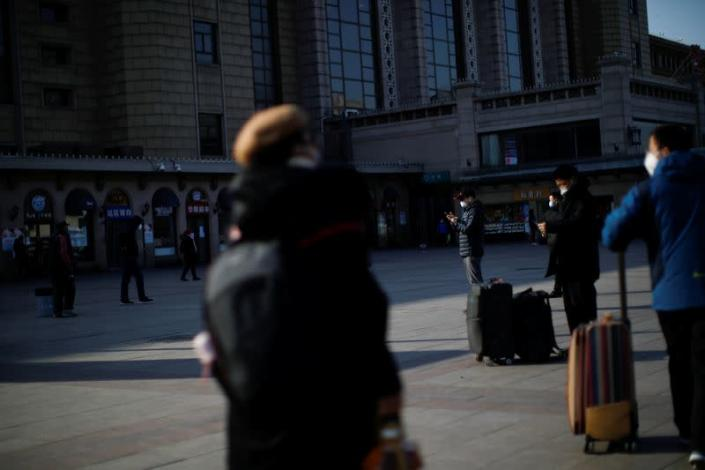 A man wearing a face mask uses his cellphone outside Beijing Railway Station as the country is hit by an outbreak of the new coronavirus, in Beijing