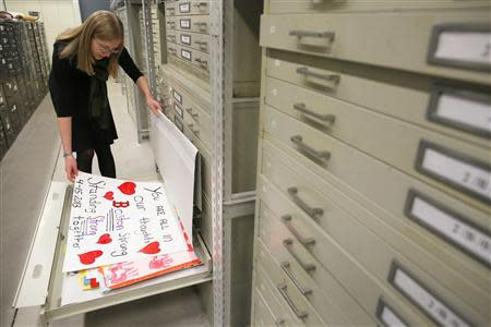 Archivist Marta Crilly looks through a file drawer of posters saved from the makeshift memorial that arose following the 2013 Boston Marathon bombings at the City Archives in Boston, Massachusetts March 27, 2014. REUTERS/Brian Snyder