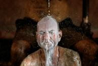 """Ashok Oza bathes in cow milk to remove cow dung from his body during """"cow dung therapy"""" on outskirts of Ahmedabad"""