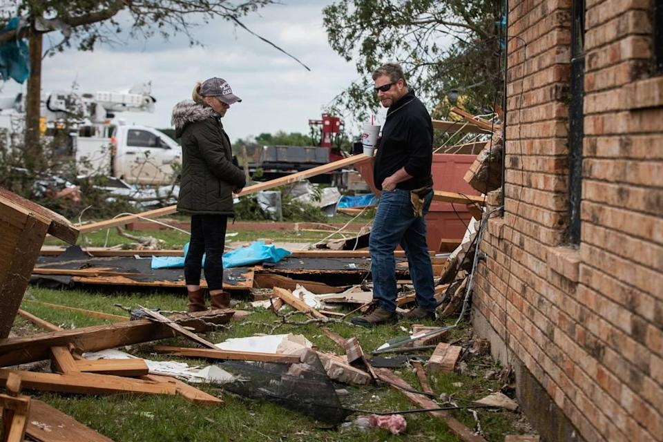 Cathy Haley and Brad Levy look over damage to the lodge at the Barn on the Brazos wedding venue Tuesday, May 4, 2021, in Blum.