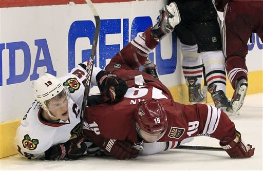 Phoenix Coyotes' Shane Doan, right, checks Chicago Blackhawks' Jonathan Toews, left, into the boards during the second period in Game 1 of an NHL hockey Stanley Cup first-round playoff series, Thursday, April 12, 2012, in Glendale, Ariz. (AP Photo/Ross D. Franklin)