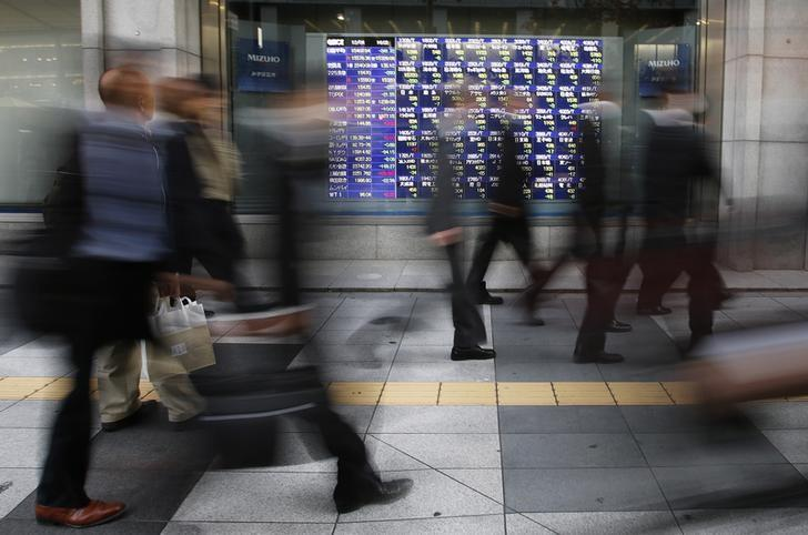 Passers-by walk past a stock quotation board outside a brokerage in Tokyo