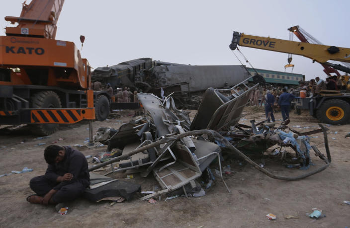 Soldiers and railway workers use crane to clear the track at the track at the site of a train collision in the Ghotki district, southern Pakistan, Monday, June 7, 2021. An express train barreled into another that had derailed in Pakistan before dawn Monday, killing dozens of passengers, authorities said. More than 100 were injured, and rescuers and villagers worked throughout the day to search crumpled cars for survivors and the dead. (AP Photo/Fareed Khan)