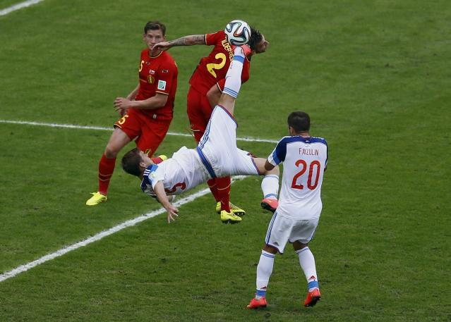 Russia's Andrey Semenov (C) attempts an overhead kick next to Belgium's Jan Vertonghen (L) and Toby Alderweireld during their 2014 World Cup Group H soccer match at the Maracana stadium in Rio de Janeiro June 22, 2014. REUTERS/Ricardo Moraes (BRAZIL - Tags: SOCCER SPORT WORLD CUP) TOPCUP