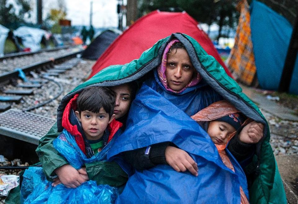 A woman and her children look on as migrants and refugees wait to cross the Greece-Macedonia border in the rain on November 27, 2015 near Gevgelija (AFP Photo/Robert Atanasovski)