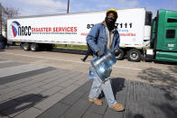 James White carries a bottle of donated water from a distribution site Thursday, Feb. 18, 2021, in Houston. Houston and several surrounding cities are under a boil water notice as many residents are still without running water in their homes. (AP Photo/David J. Phillip)