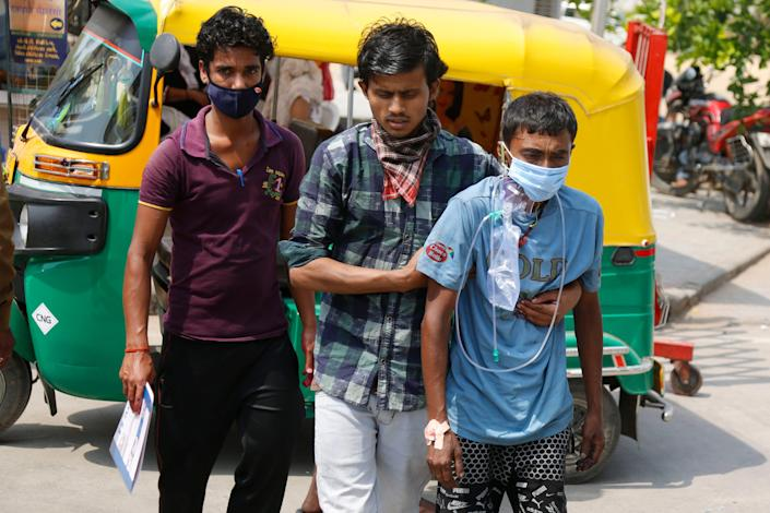 Relatives arrive with a COVID-19 patient at a dedicated COVID-19 government hospital in Ahmedabad, India,  April 27, 2021. Coronavirus cases in India are surging faster than anywhere else in the world.