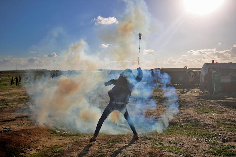 A Palestinian uses a slingshot to throw tear gas towards Israeli forces during a demonstration along the Gaza border on January 18, 2019 (AFP Photo/SAID KHATIB)