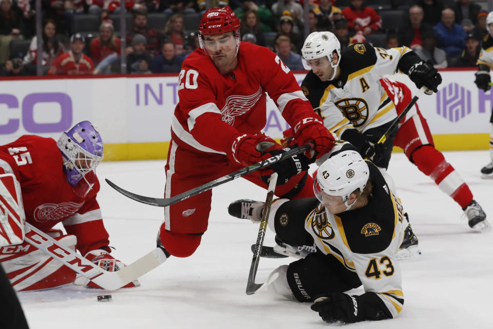 Detroit Red Wings defenseman Dylan McIlrath (20) checks Boston Bruins left wing Danton Heinen (43) in front of the net during the first period of an NHL hockey game, Friday, Nov. 8, 2019, in Detroit. (AP Photo/Carlos Osorio)