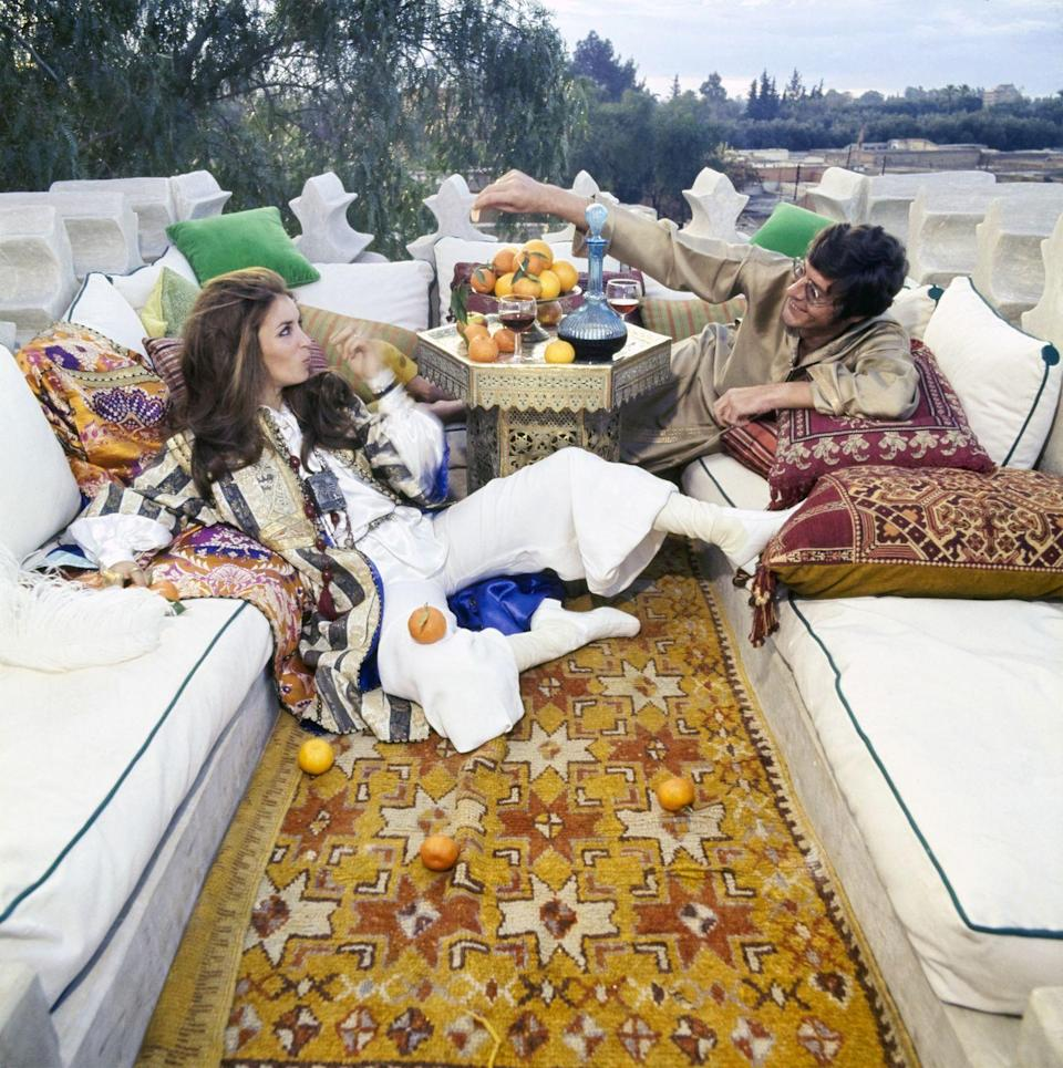 """<p>Paul and Talitha Getty made Morocco their home in the late '60s. The son of American tycoon J. Paul Getty purchased the Marrakech riad, <a href=""""https://www.wsj.com/articles/an-exclusive-tour-of-a-french-iconoclasts-moroccan-getaway-1505210280"""" rel=""""nofollow noopener"""" target=""""_blank"""" data-ylk=""""slk:Palais de la Zahia"""" class=""""link rapid-noclick-resp"""">Palais de la Zahia</a>, in 1966. Here, they are photographed on their rooftop deck in 1969. </p>"""