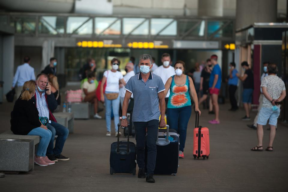 """Passengers wearing face masks walk with their suitcases at Malaga-Costa del Sol airport after the country reopened its borders amid the coronavirus disease (COVID-19) outbreak. Spain has ended the alarm state after more than three months of lockdown. The Spanish government says that from now on people will live under a """"new normality"""", using face masks and keeping safe distances during their daily life. (Photo by Jesus Merida / SOPA Images/Sipa USA)"""