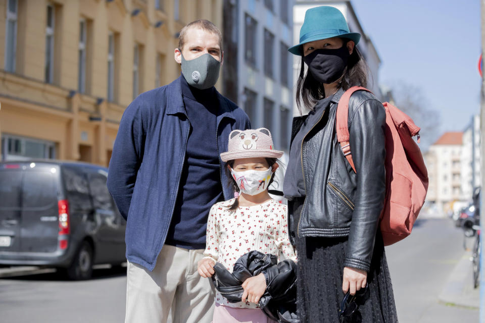 06 April 2020, Berlin: Vinzenz Wagner (l-r), the 7-year-old Mika and Lih Wong stand together in Berlin-Mitte with protective masks for a photo. In order to slow down the spread of the corona virus, the German government has considerably restricted public life. Photo: Christoph Soeder/dpa (Photo by Christoph Soeder/picture alliance via Getty Images)