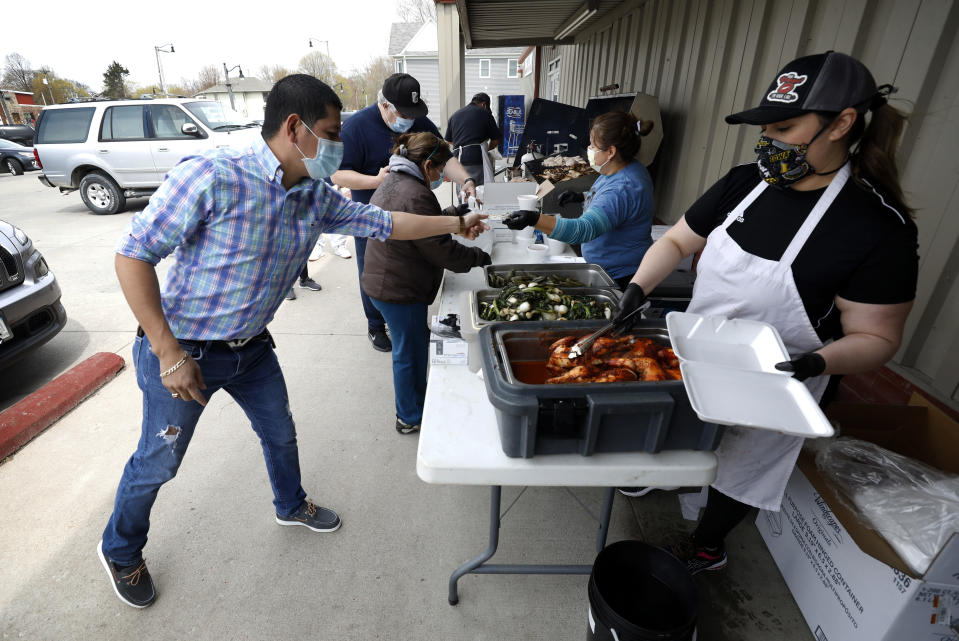 Vanessa Salais, right, of West Liberty, Iowa, serves chicken dinners during a fundraiser for the Omar Martinez family, Saturday, April 25, 2020, in West Liberty, Iowa. Martinez's family had been living the American dream after immigrating from Mexico in the 1990s and settling in this small town in eastern Iowa, but their lives fell apart after coronavirus infections spread from his mother to his sister and his father. (AP Photo/Charlie Neibergall)