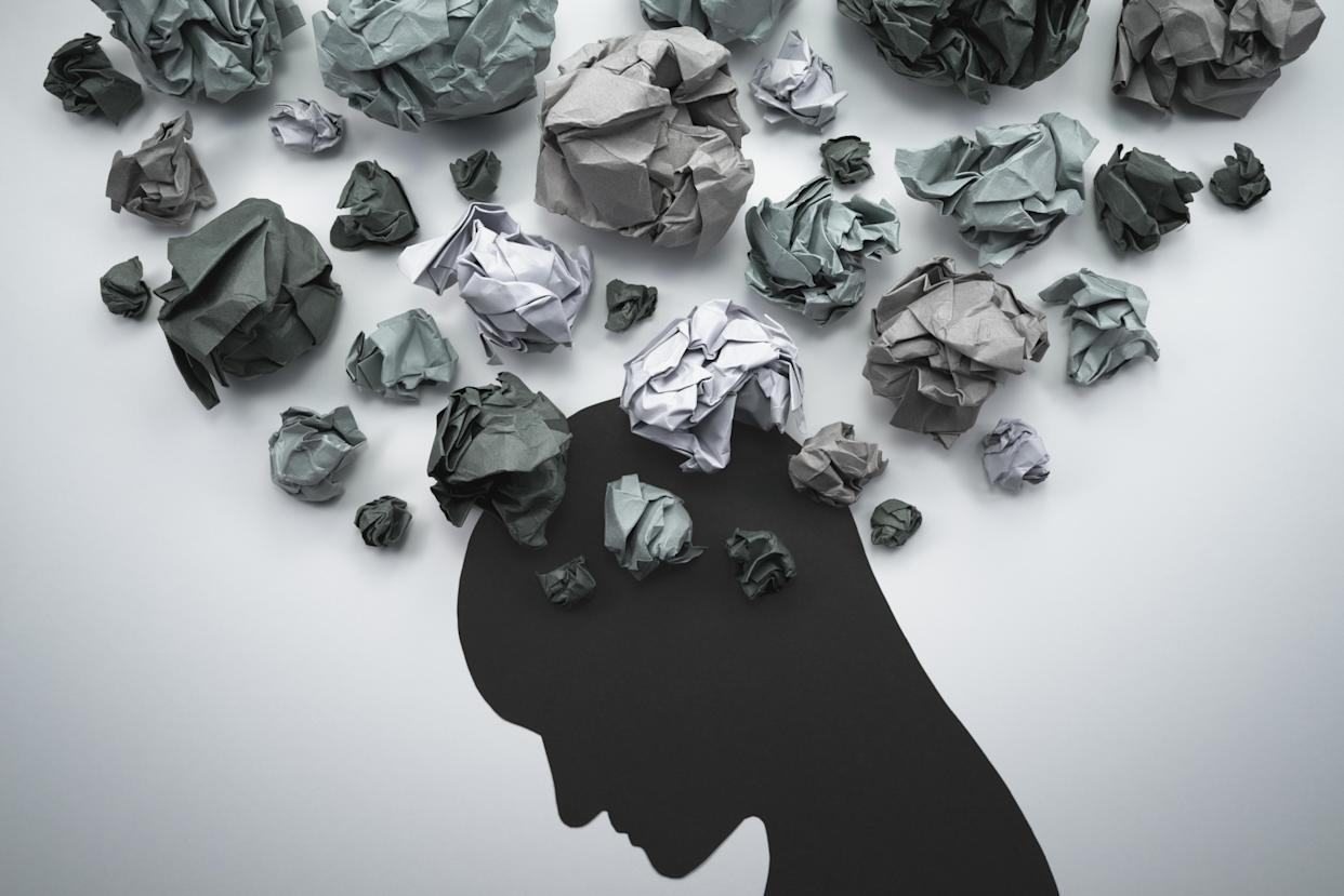 Concept image of anxiety and negative emotion. Waste paper and head silhouette. (Getty Images)