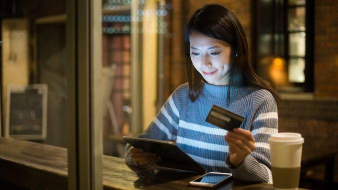 woman using tablet while shopping with credit card