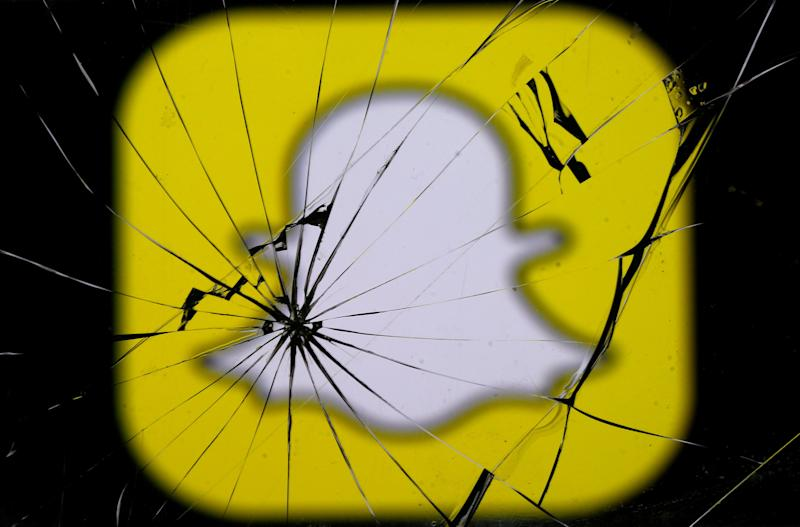 Snapchat logo is seen through broken glass in this illustration picture, May 11, 2017. REUTERS/Dado Ruvic/Illustration