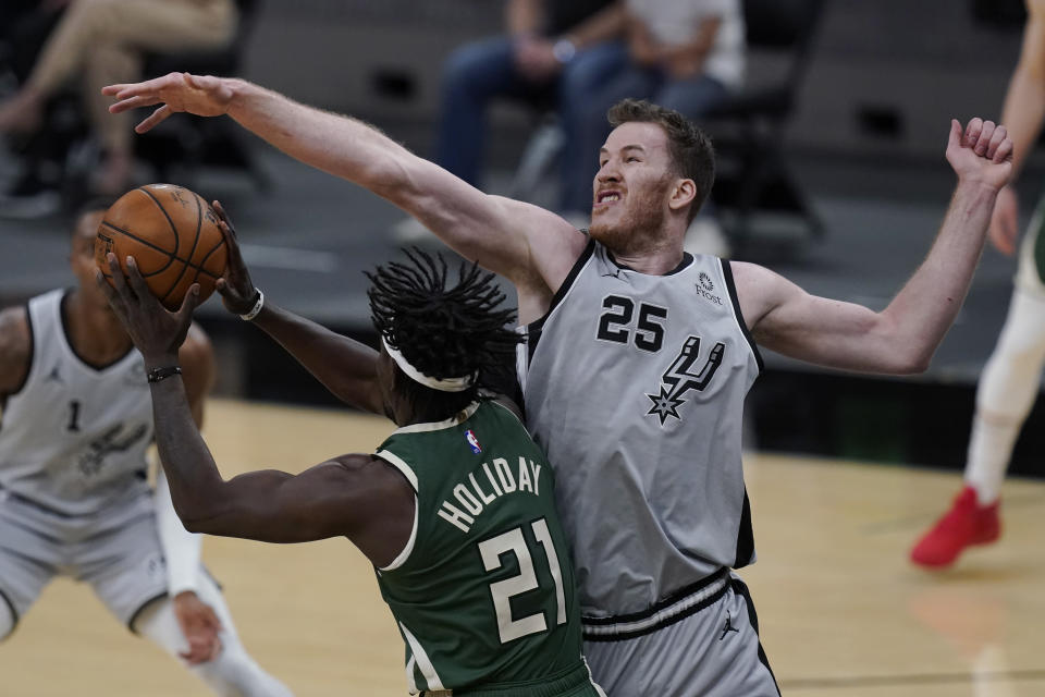 Milwaukee Bucks guard Jrue Holiday (21) is defended by San Antonio Spurs center Jakob Poeltl (25) during the first half of an NBA basketball game in San Antonio, Monday, May 10, 2021. (AP Photo/Eric Gay)