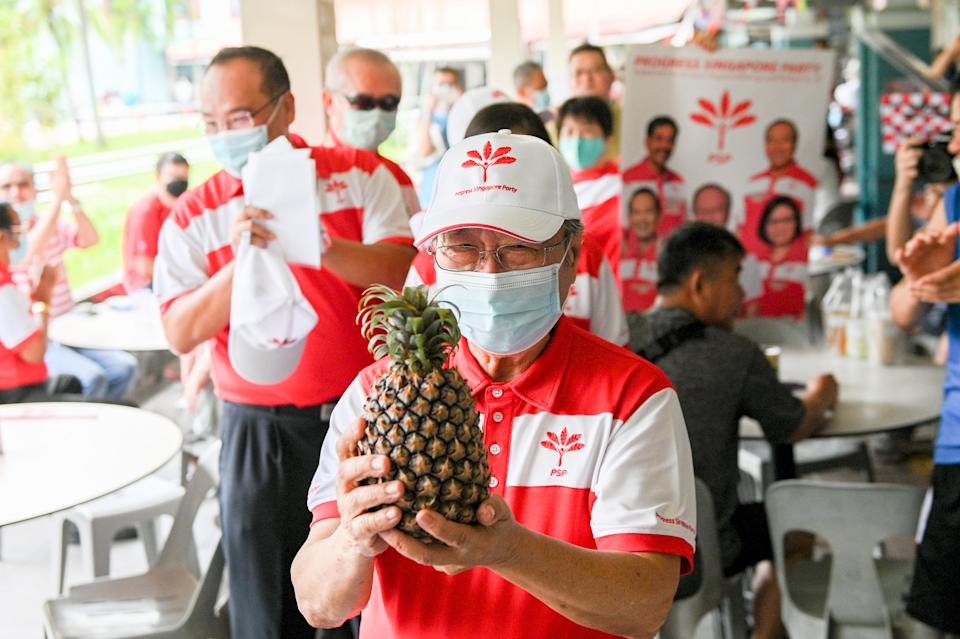 PSP chief Tan Cheng Bock carrying a pineapple he received seen during a party walkabout in the Nanyang area on Saturday (4 July). (PHOTO: Joseph Nair for Yahoo News Singapore)