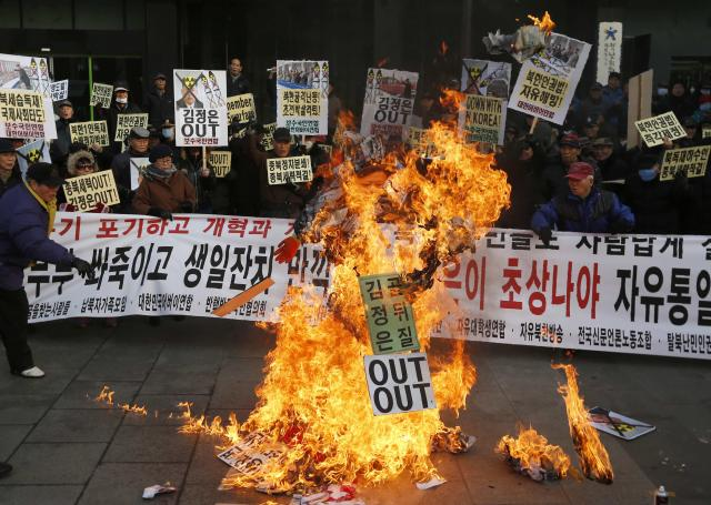 Protesters burn an effigy of North Korean leader Kim during a rally denouncing former U.S. basketball star Dennis Rodman's visit to North Korea and Kim on Kim's birthday in central Seoul