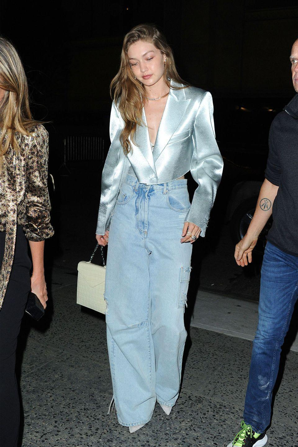 """<p>In a silver cropped blazer and high-waisted oversize jeans by Off-White and a <a href=""""https://www.net-a-porter.com/us/en/product/1113412/BY_FAR/allegra-croc-effect-leather-shoulder-bag"""" rel=""""nofollow noopener"""" target=""""_blank"""" data-ylk=""""slk:cream crocodile bag by By Far"""" class=""""link rapid-noclick-resp"""">cream crocodile bag by By Far</a>.</p>"""