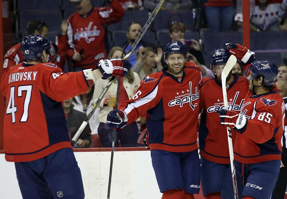 Washington Capitals defenseman Michal Cajkovski (47), from Slovakia, comes in to celebrate a goal by right wing Eric Fehr (16), with left wing Dane Byers (50) and center Mathieu Perreault (85) in the first period of a preseason NHL hockey game against the Philadelphia Flyers, Friday, Sept. 27, 2013, in Washington. (AP Photo/Alex Brandon)
