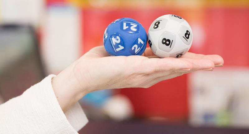 A woman holds to Powerball balls.