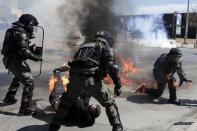 A protester, bottom, and riot policeman react after catching fire from a gasoline bomb during a protest in the the northern city of Thessaloniki, Greece, Thursday, April 15, 2021. The protester was arrested on suspicion of throwing a gasoline bomb, authorities said. Clashes between small groups of demonstrators and police broke out in the northern Greek city of Thessaloniki at the end of a march to protest a new law allowing the policing of university campuses. (AP Photo/Achilleas Chiras)
